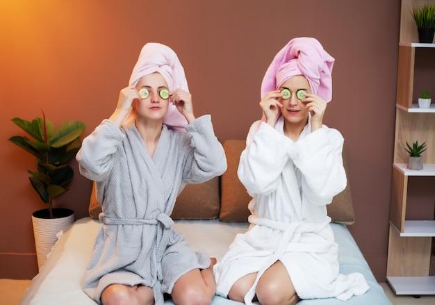 Deux copines avec des serviettes sur la tête, faisant des traitements de spa à la maison au lit