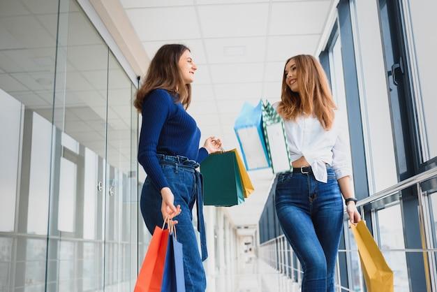Deux copines sur shopping à pied sur le centre commercial avec des sacs