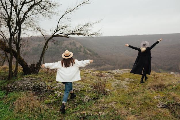 Deux copines vont avec les mains en regardant les montagnes.