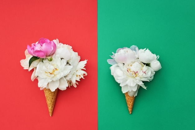 Deux cornets de crème glacée gaufres avec des fleurs de pivoine blanche sur table vert rouge. concept d'été. copie