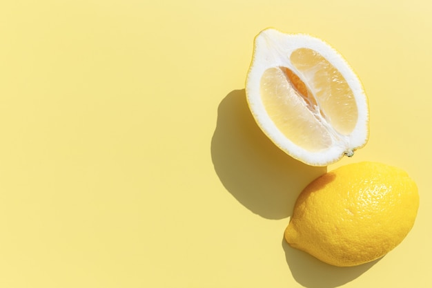 Deux coupes de citron coupées en deux avec une ombre sur fond jaune. concept d'alimentation saine, de voyage ou de vacances