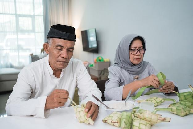 Deux couples d'âge mûr faisant du ketupat pour l'aïd fitri moubarak à la maison