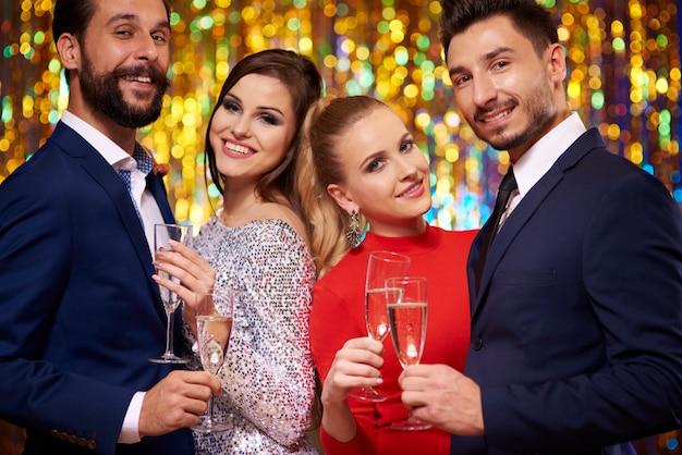 Deux couples sur le mur de paillettes, célébrant la nouvelle année
