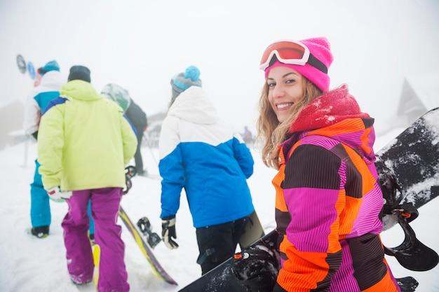 Deux couples s'amusant et faisant du snowboard