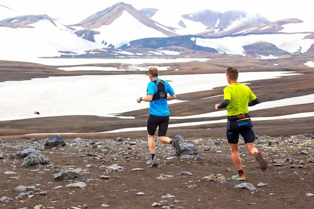 Deux coureurs d'athlètes courent un marathon de montagne dans le terrain enneigé de landmannalaugar