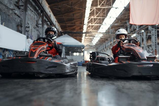 Deux coureurs de kart se battent pour la victoire sur les genoux, vue de côté, karting auto sport indoor. course de vitesse sur piste de karting fermée avec barrière de pneu. compétition de véhicules rapide