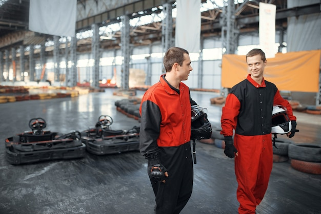 Deux coureurs de kart tiennent des hemets, karting auto sport indoor. course de vitesse sur piste de karting étroite avec barrière de pneu. compétition de véhicules rapides