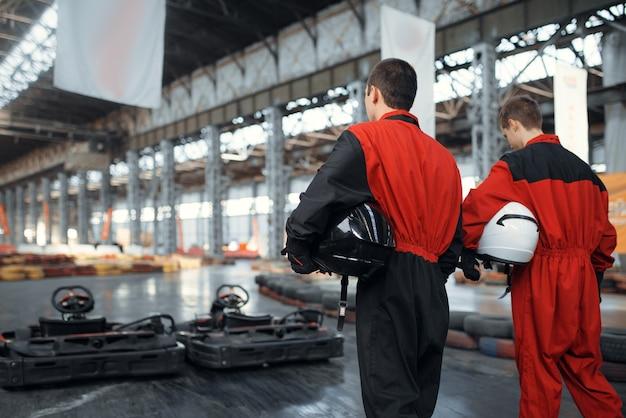 Deux coureurs de kart tiennent des hemets, vue arrière, karting auto sport indoor. course de vitesse sur piste de karting étroite avec barrière de pneu. compétition de véhicules rapides, loisirs à haute adrénaline