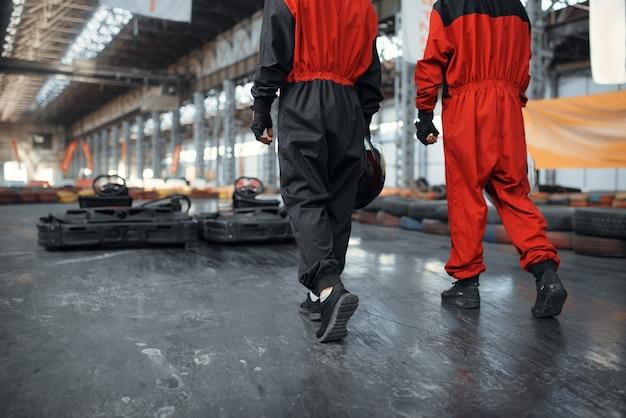 Deux coureurs de kart tiennent des hemets, vue arrière, karting auto sport indoor. course de vitesse sur piste de karting étroite avec barrière de pneu. compétition de véhicules rapides