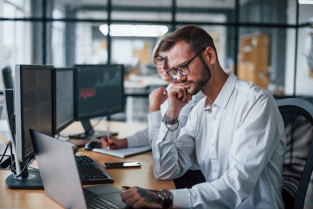 Deux courtiers en vêtements formels travaillent au bureau avec le marché financier.