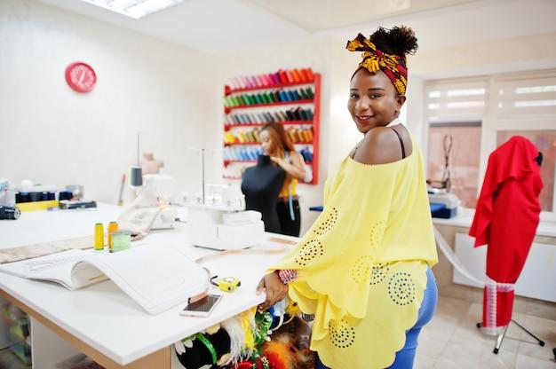 Deux couturière africaine femme coud des vêtements sur machine à coudre au bureau de tailleur. filles de couturière noire.