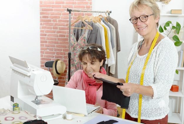 Deux couturières gaies travaillant ensemble dans leur atelier