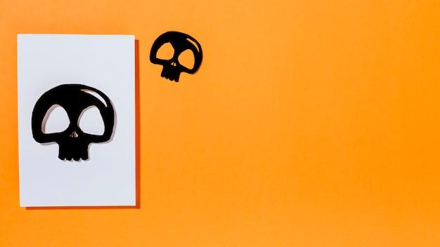 Deux crânes noirs avec un morceau de papier