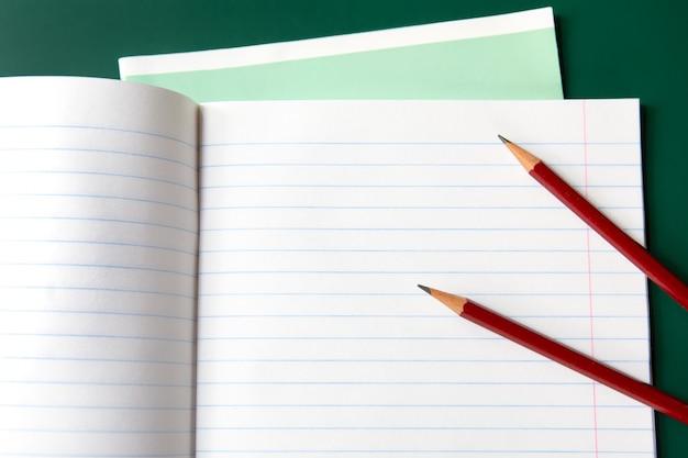 Deux crayons sur un cahier ligné.