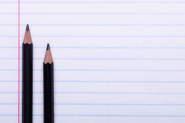 Deux crayons de graphite noir sur une feuille blanche en ligne espace copie retour à l'école, concept de l'éducation