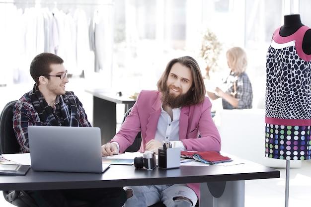 Deux créateurs de mode discutant des conceptions des nouveaux modèles.