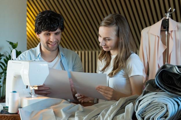 Deux créateurs de mode, un homme et une femme, regardaient des échantillons de croquis dans un atelier de couture