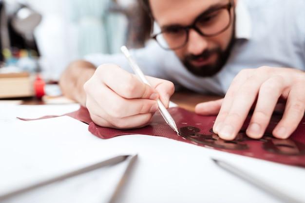 Deux créateurs de mode réalisant une découpe sur du cuir