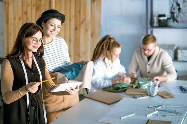 Deux créateurs de mode avec tablette discutant des nouvelles collections et tendances sur fond de collègues