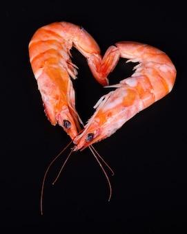 Deux crevettes formant un coeur sur un fond noir.