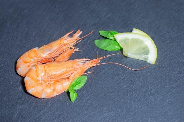 Deux crevettes rouges cuites au basilic vert et citron sur fond noir