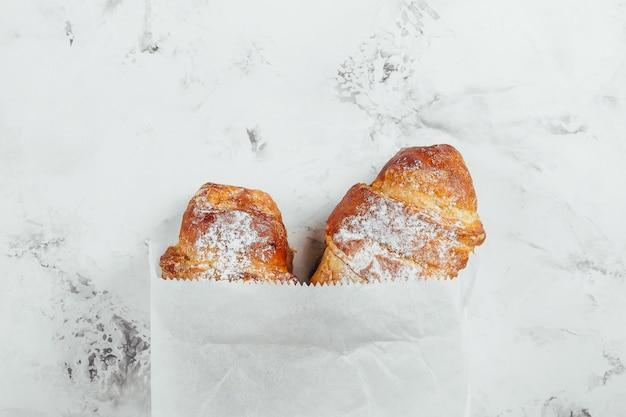 Deux croissants frais dans un sac en papier sur un fond de marbre, vue de dessus, espace de copie