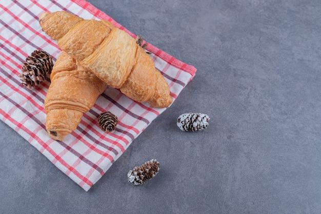 Deux croissants frais fraîchement sortis du four sur fond gris.