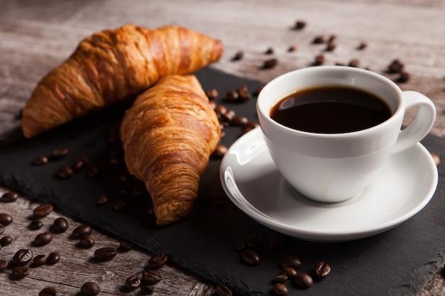 Deux croissants frais et une tasse de café sur une table en pierre sombre. dessert délicieux.
