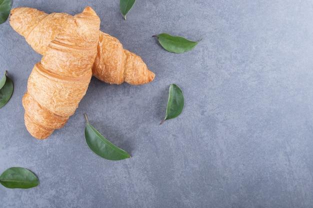 Deux croissants français frais avec des feuilles décoratives sur fond gris