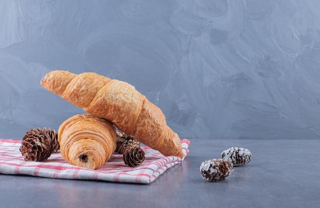 Deux croissants français frais avec pomme de pin décorative.