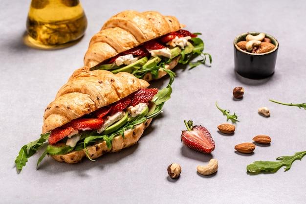 Deux croissants garnis. salade de roquette, fraises et fromage brie, camembert