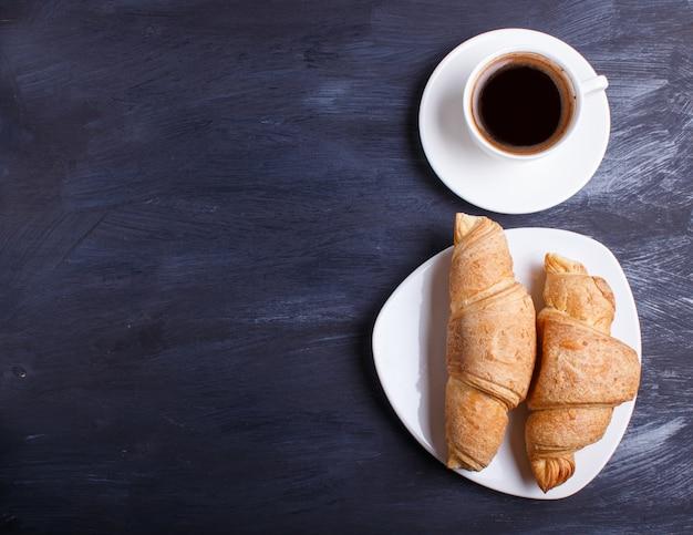 Deux croissants avec une tasse de café sur une plaque blanche sur un fond en bois noir