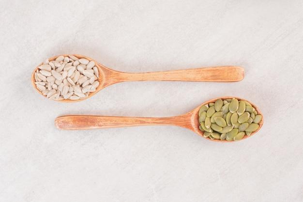 Deux cuillère en bois de graines de tournesol et de citrouille sur une surface blanche.
