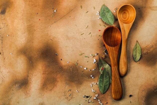 Deux cuillères en bois, feuilles de laurier, poivre et sal sur vieux papier médiéval