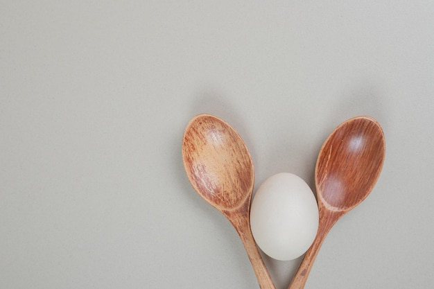 Deux cuillères en bois avec oeuf blanc de poule.