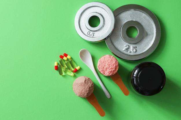 Deux cuillères à mesurer de protéines de lactosérum et de disques sur une table