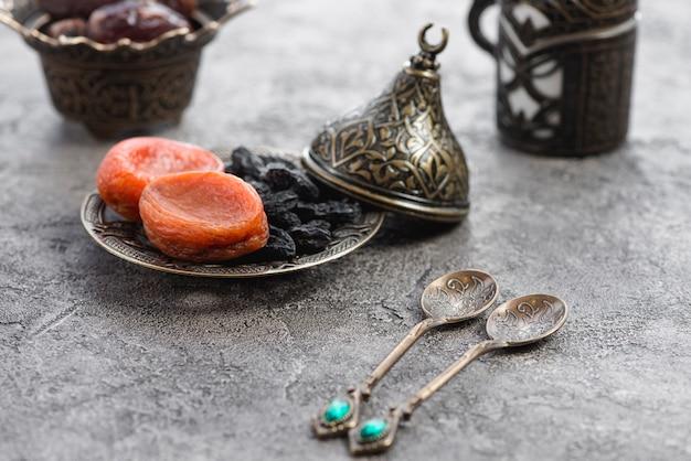 Deux cuillères métalliques traditionnelles en face de l'abricot séché et raisin noir sur plaque