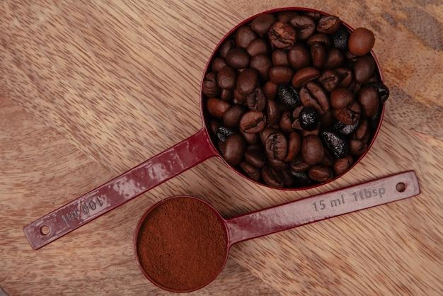 Deux cuillères rouges avec des grains de café et du café moulu