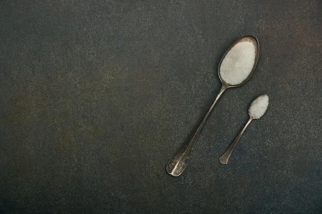 Deux cuillères de sucre et de sel sur la table