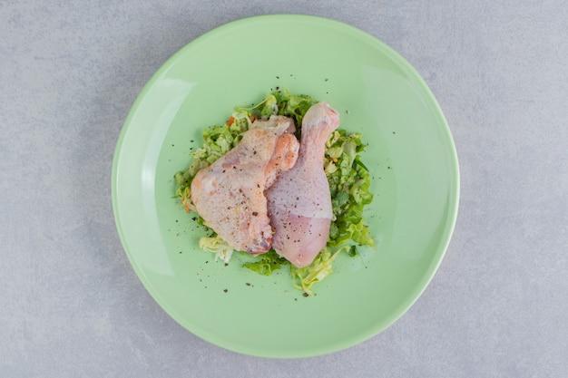 Deux cuisses de poulet marinées dans l'assiette, sur la surface blanche