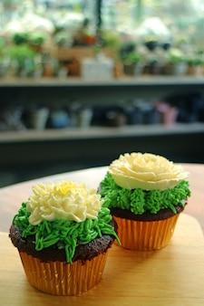 Deux cupcakes garnis de crème fouettée en forme de fleur servis sur une table en bois