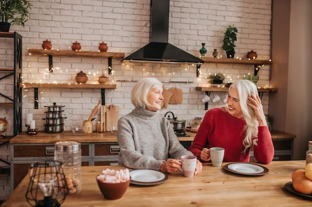 Deux dames positives aux cheveux gris matures ayant une conversation