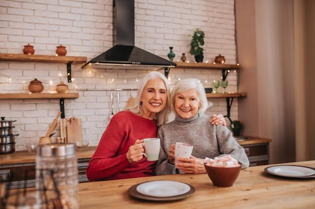 Deux dames positives aux cheveux gris matures prenant le petit déjeuner
