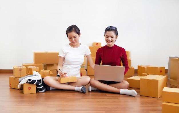 Deux dames vendant en ligne au bureau à la maison, entreprise partenaire, travaillant ensemble