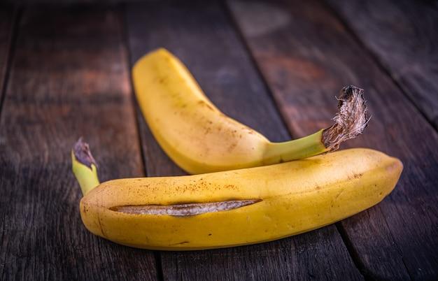 Deux délicieuses bananes mûres aux pelures craquelées se trouvent sur de vieilles planches de bois