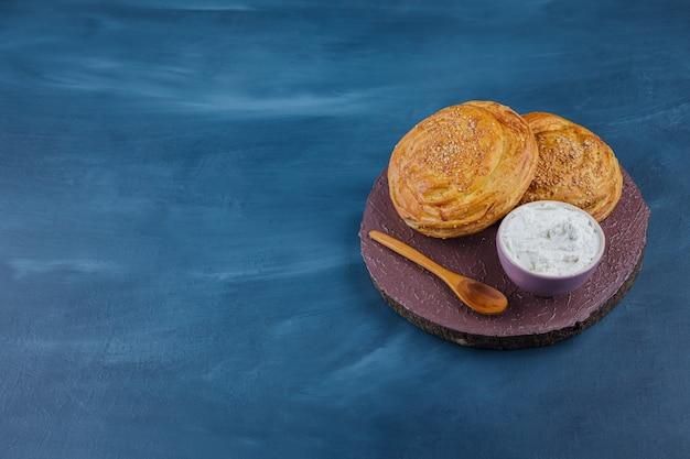 Deux délicieuses pâtisseries traditionnelles et crème sure sur morceau de bois.