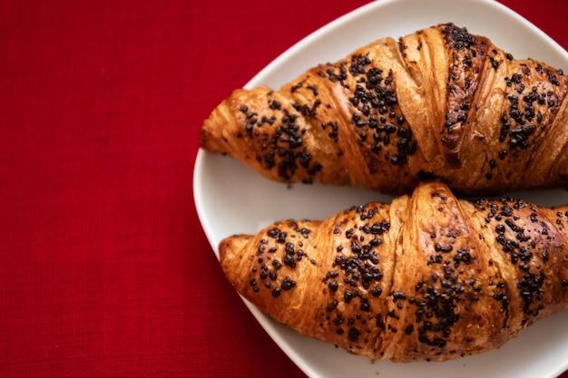 Deux délicieux croissants aux pépites de chocolat sur une vue de dessus de plaque blanche