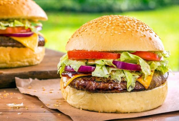 Deux délicieux hamburgers sur un bureau en bois avec une nature d'herbe verte.
