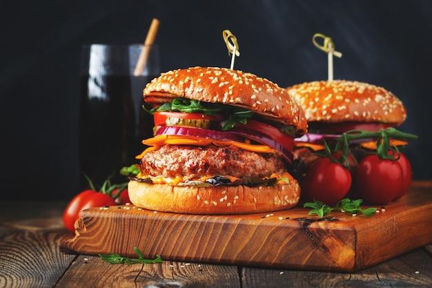 Deux délicieux hamburgers faits maison de bœuf, de fromage et de légumes sur une vieille table en bois. gros plan de gros aliments malsains..