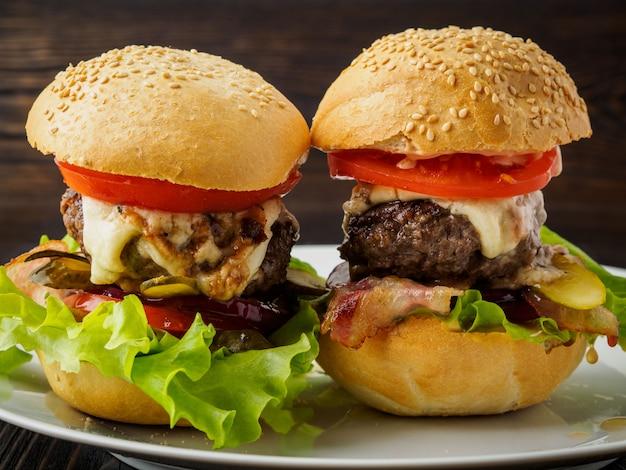 Deux délicieux hamburgers faits maison avec une escalope de boeuf, du fromage, de l'oignon, des tomates et de la laitue